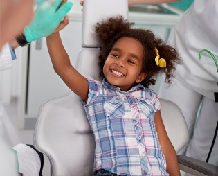 Little girl giving dentist high five