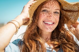 woman in beach hat smiling